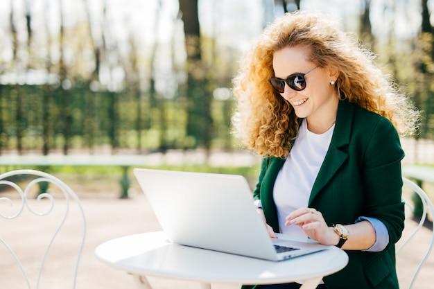 彼女のラップトップを使用して彼女のボーイフレンドに楽しい何かを読んで満足している彼女のラップトップを使用して公園の机に座って魅力的な若い巻き毛の女性の屋外のポートレート。