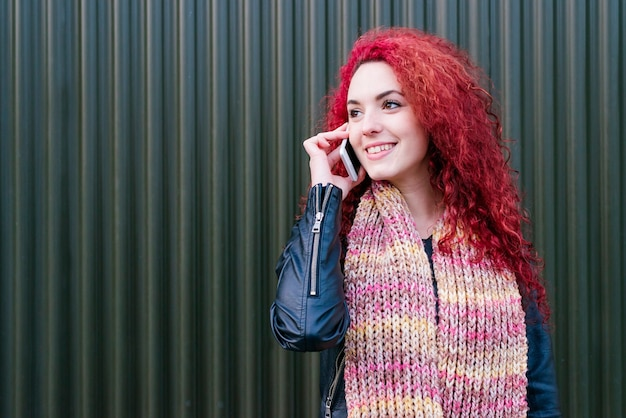 通りで携帯電話を持つ魅力的な若い女性の屋外の肖像画。
