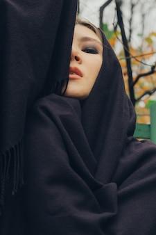 黒いスカーフで覆われた美しいアジアの女の子の屋外の肖像画。
