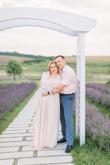 라벤더 밭에 있는 나무 아치 아래 서 있는 아름다운 쾌활한 낭만적인 성숙한 커플, 남자가 여자를 껴안고 있는 야외 초상화