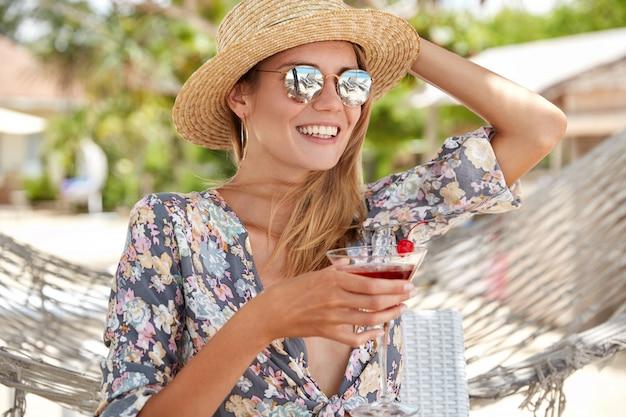 Открытый портрет красивой женщины чувствует себя расслабленным, когда пьет свежий коктейль, носит модную шляпу и солнцезащитные очки, сидит возле гамака, хорошо отдыхает в солнечную летнюю погоду. концепция отдыха