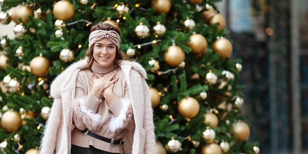 装飾されたモミの木に対する美しい少女の屋外の肖像画。クリスマス、正月、冬