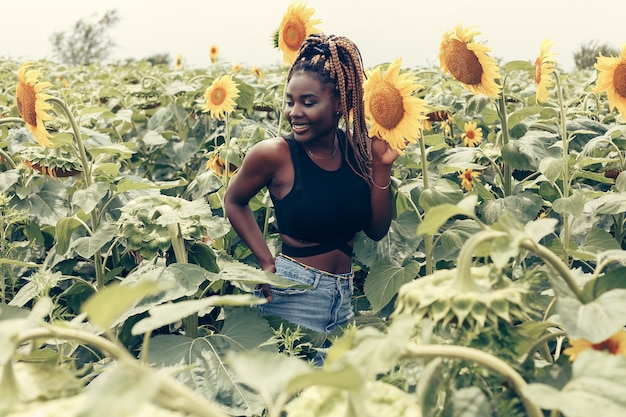 Открытый портрет красивой счастливой смешанной расы афро-американской девушки подростка девушки молодой женщины в поле желтых цветов на закате золотой вечернее солнце
