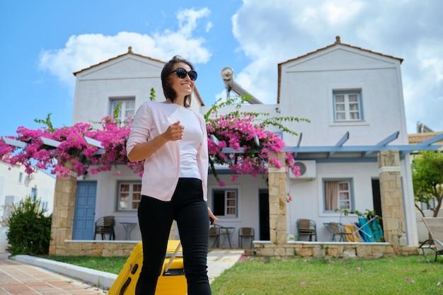 ホテルの海のスパリゾート、コピースペースでスーツケースを持つ美しい観光客の女性の屋外の肖像画。旅行、休暇、レジャー、週末、人々