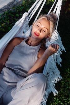 ヴィラホテル、海側の外で休暇中にハンモックで赤い口紅と古典的なジャンプスーツの白人女性の屋外の肖像画