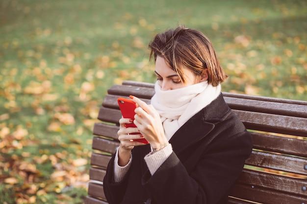 검은 겨울 코트와 휴대 전화와 함께 공원에서 벤치에 앉아 스카프를 착용하는 백인 여자의 야외 초상화.