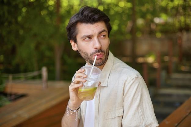 緑の街の庭でポーズをとって、脇を見て、わらでレモンを飲む、黒髪の魅力的な若いひげを生やした男性の屋外の肖像画