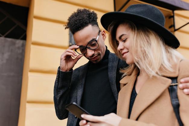 아프리카 남자 친구에 대 한 새로운 전화를 보여주는 쾌활 한 백인 여자의 야외 초상화. 도시 거리에 금발 여자와 재미 안경에 세련 된 흑인 젊은 남자.