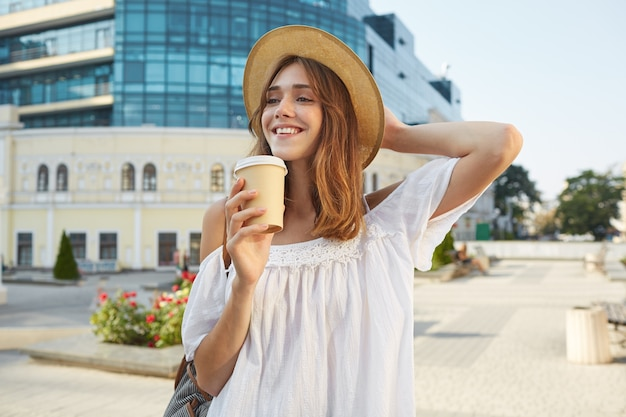 Открытый портрет жизнерадостной очаровательной молодой женщины носит стильную летнюю шляпу и белое платье, чувствует себя расслабленно, стоя и пьет кофе на вынос на улице в городе