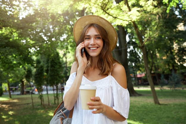 陽気な魅力的な若い女性の屋外の肖像画は、スタイリッシュな夏の帽子と白いドレスを着て、リラックスした気分で、街の路上でテイクアウトのコーヒーを飲みながら立っています