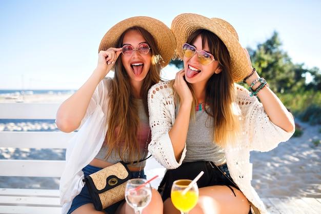 Открытый портрет компании счастливых смешных девушек-хипстеров сходит с ума в пляжном кафе, пьет вкусные коктейли, смеясь и улыбаясь, винтажные яркие летние наряды в стиле бохо, отношения и веселье.