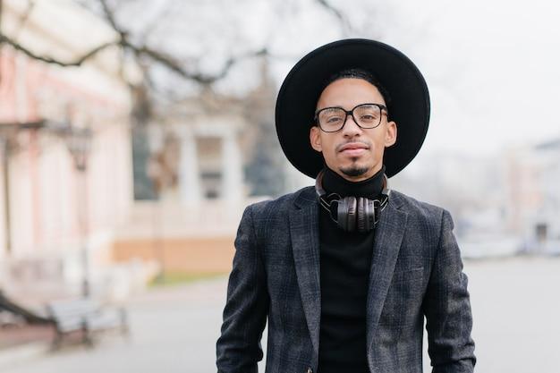 큰 음악 헤드폰을 착용하는 어두운 피부를 가진 호기심 남자의 야외 초상화. 흐림 거리에 서있는 검은 복장에 심각한 아프리카 남성 모델의 사진