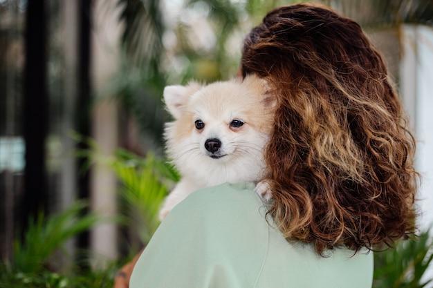 巻き毛のヨーロッパの日焼けした女性の屋外の肖像画は幸せなペットの犬のポメラニアンスピッツを保持します