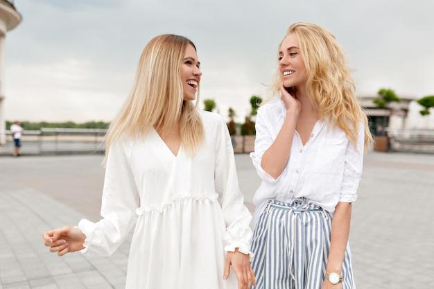 通りを歩き、曇りの夏の日に笑いながら夏の街でリラックスして外で楽しんでいるかわいい女性の屋外の肖像画。外の2人のスタイリッシュな女の子
