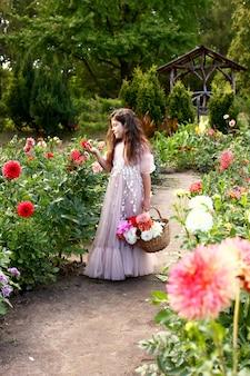 ダリアの花、秋の庭のカラフルな花束を保持しているかわいい女の子の屋外のポートレート