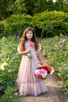 ダリアの花のカラフルな花束を保持しているかわいい女の子の屋外のポートレート
