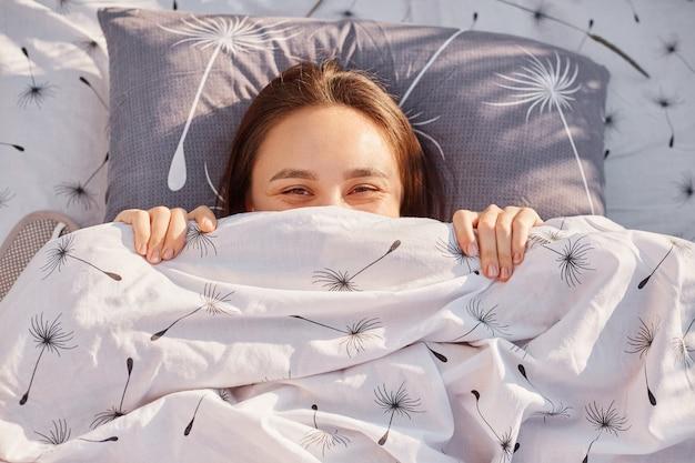 Открытый портрет темноволосой женщины, лежащей в постели на открытом воздухе под солнечными лучами, пряча лицо под одеялом, выражающей счастье, расслабляющейся и наслаждающейся природой.