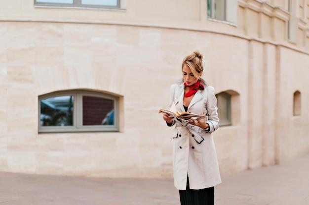 路上に立って見下ろしているロングコートで失望したヨーロッパの女性の屋外のポートレート