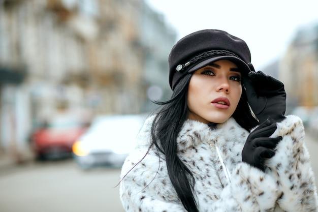 スタイリッシュなキャップと暖かいコートを着ているエレガントなブルネットの女性の屋外の肖像画。テキスト用のスペース