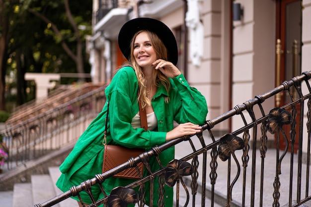 Открытый портрет элегантной красивой женщины, позирующей на улице в европейском городе, стильной шляпе и аксессуарах.