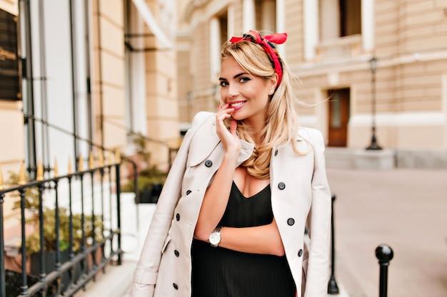ブロンドの髪の赤いリボンとエレガントな笑顔の女性の屋外の肖像画。ベージュのコートとトレンディな腕時計の魅力的な若い女性が通りの真ん中でポーズをとって笑っています。