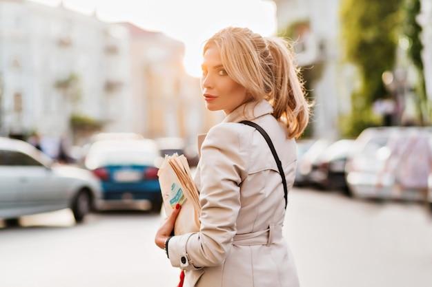Открытый портрет элегантной юной женщины, несущей газеты после работы и позирующей с серьезным выражением лица
