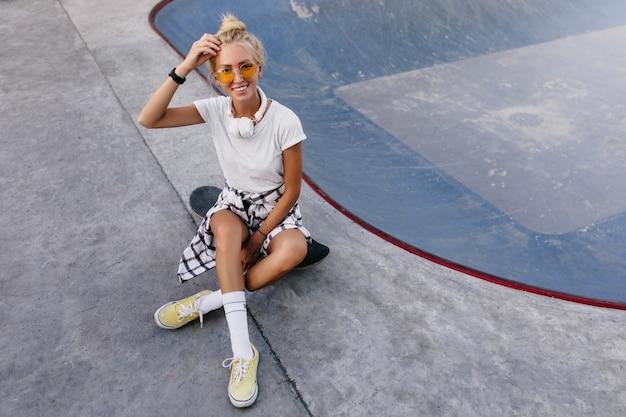 スケートボードに座っている感情的な女性の屋外の肖像画。スケートパークで時間を過ごす白い靴下とスポーツシューズで身も凍るような日焼けした女性。