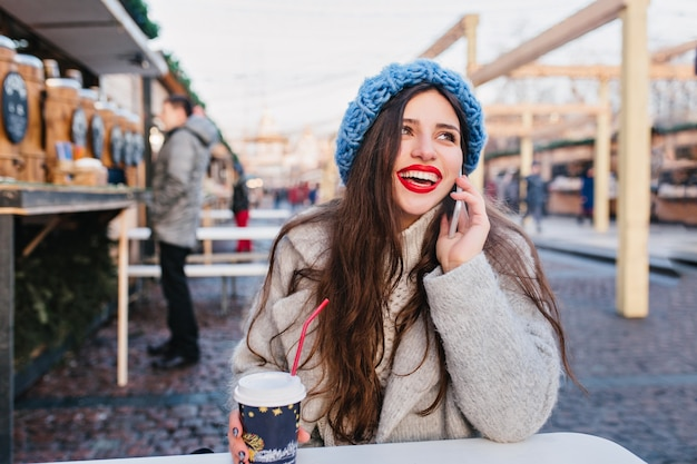 暖かい日に冬の週末を楽しんでいるウールのコートで興奮しているブルネットの少女の屋外のポートレート。ぼかし通りでポーズかわいい青い帽子の長い髪の白人女性の写真