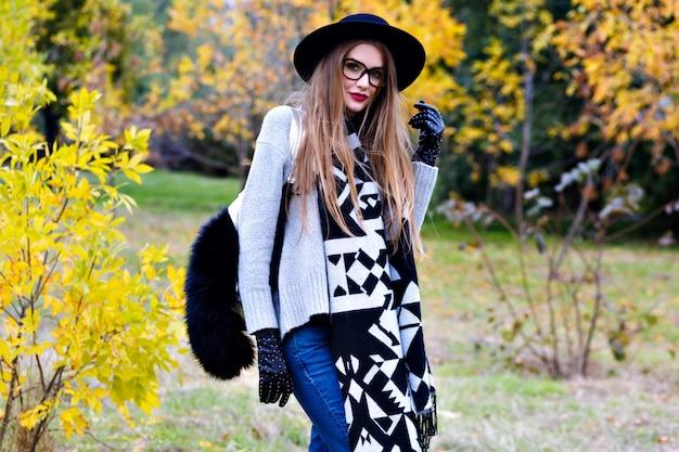 興奮した少女の屋外のポートレートは、流行のつばを着て、自信を持ってポーズで立っています。秋の自然の背景にポーズをとってメガネの魅力的な若い女性。