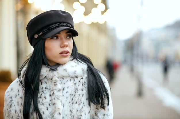 スタイリッシュなキャップと暖かいコートを着ているファッショナブルなブルネットの女性の屋外の肖像画。テキスト用のスペース