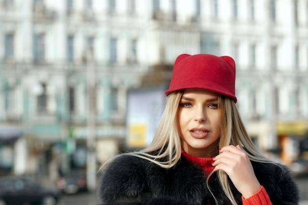スタイリッシュな赤いキャップとニットのスカーフを身に着けているファッショナブルな女の子の屋外の肖像画。テキスト用のスペース