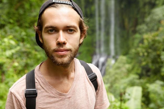 滝とエキゾチックな緑の自然に逆らって立っている黒いスナップバックを後ろに身に着けているファッショナブルな若いひげを生やした男の屋外のポートレート。熱帯雨林で休暇を過ごす白人観光客