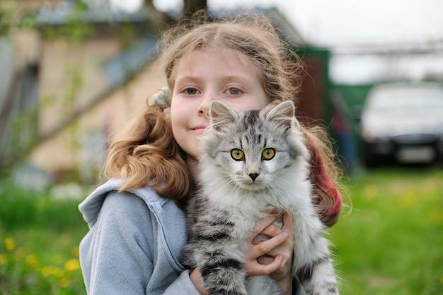 Открытый портрет девочки, держащей на руках любимого питомца, пушистого серого кота