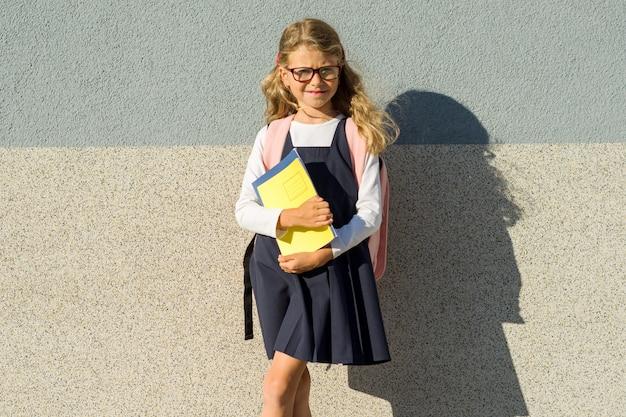 メガネをかけて、バックパック、本、ノートブックの女の子小学生の屋外のポートレート