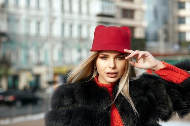 スタイリッシュな赤いキャップとニットのスカーフを身に着けている魅力的な女の子の屋外の肖像画