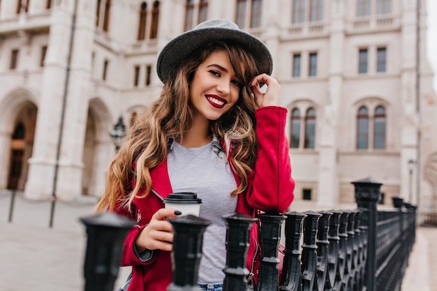 Открытый портрет гламурной женщины с волнистой прической, пьющей кофе