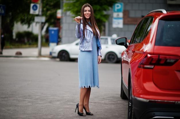 オレンジ色のsuv車の近くでポーズをとってゴージャスな女性の屋外の肖像画と手元のキーを表示