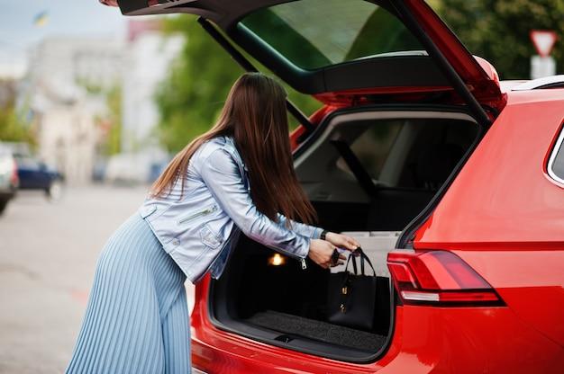 開いた車のトランクとオレンジ色のsuv車の近くでポーズをとってゴージャスな女性の屋外の肖像画