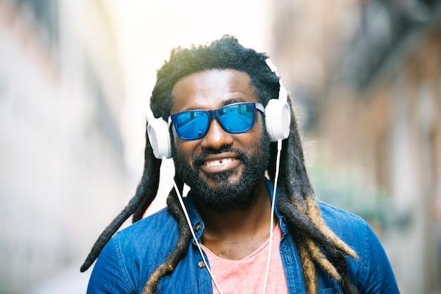 音楽を聞いているハンサムなアフリカの若い男の屋外の肖像画。