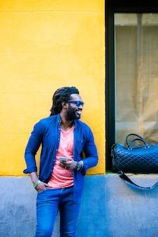 通りでモバイルを使用してハンサムなアフリカの若い男の屋外の肖像画。