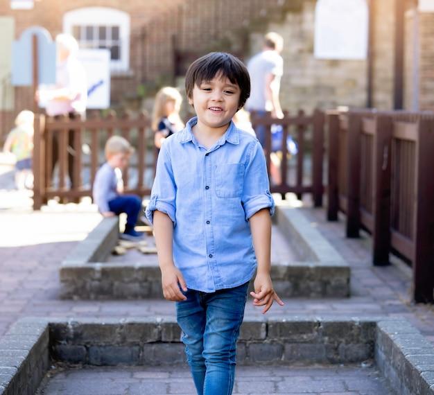 ハンサムな男の子の笑顔と一人で立っているハンサムな男の子の屋外のポートレート、率直なショット幸せな子供の背景を遊んでいるぼやけた子供たちと外を歩いて、子供の夏の休日に家族と一緒にリラックス。