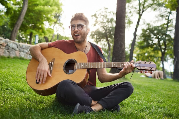 公園の芝生の上に座って、ギターを弾くハンサムな屈託のない流行に敏感な男の屋外のポートレート