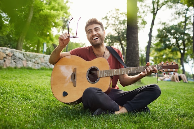 公園の芝生の上に座って、ギターを弾くハンサムな流行に敏感な男の屋外のポートレート