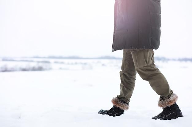 코트와 스카프에 잘생긴 남자의 야외 초상화. 겨울 숲에서 수염 난된 남자입니다.
