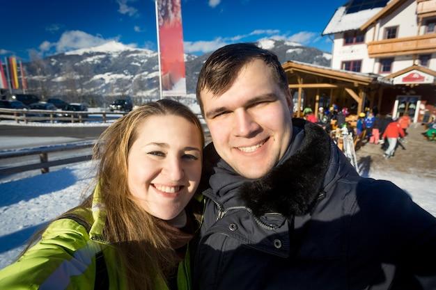 Открытый портрет счастливой улыбающейся влюбленной пары на горнолыжном курорте