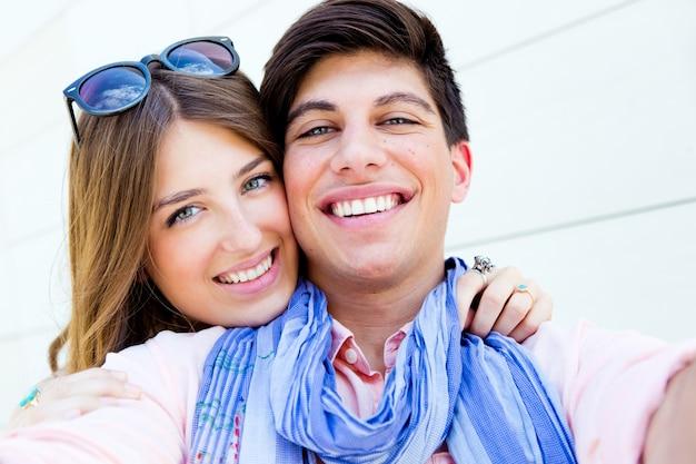 ストリートでスマートフォンで写真を撮る幸せな若いカップルの屋外の肖像画
