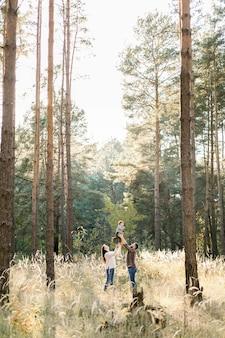 Открытый портрет счастливых молодых родителей, весело проводящих время и поднимающих своего маленького симпатичного маленького сына, во время прогулки в осеннем лесу в солнечный день