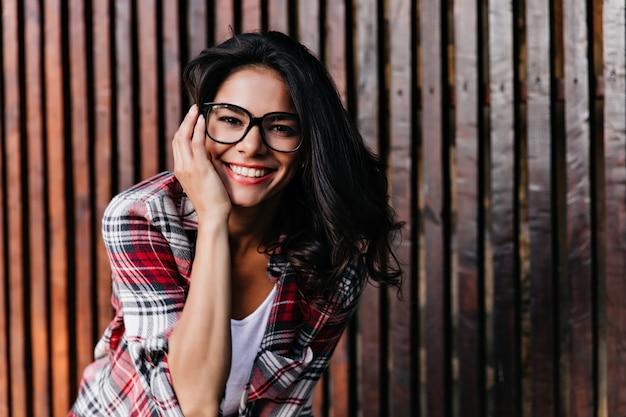 나무 벽에 고립 된 평온한 여자 웃음의 야외 초상화. 울타리 근처에 서 안경에 행복 무두 질된 소녀.