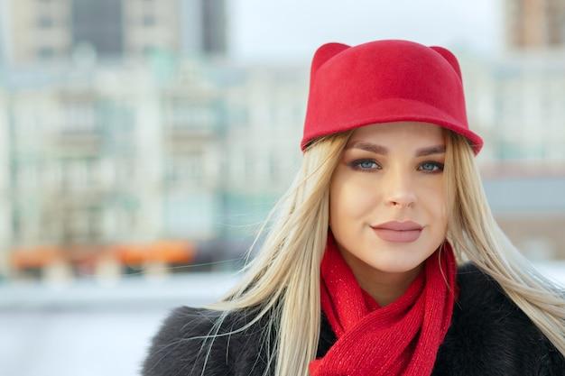 スタイリッシュな赤い帽子とニットのスカーフを身に着けている素敵な女の子の屋外の肖像画