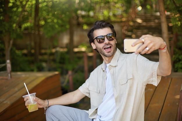 緑豊かな街の公共の場所でスマートフォンを使って自分撮りをしている素敵な若いひげを生やした男性の屋外の肖像画、大きな口を開いて、レモネードのカップを手に持って見ています